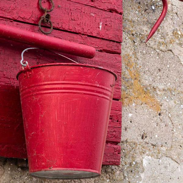 roter Eimer vor alter Betonwand für strassburger | gmbh vorbeugenden Brandschutz